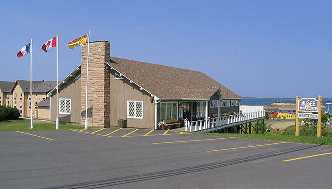 The image shows the exterior of the Musee Acadien de Caraquet