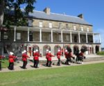 Exterior of the Fredericton Region Museum, with the Queen's guards marching in front of it.